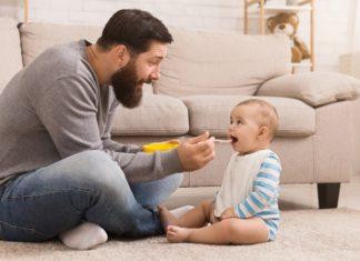 Hombre y bebé sentados en el suelo, el papá le ofrece papilla, que el bebé acepta contento